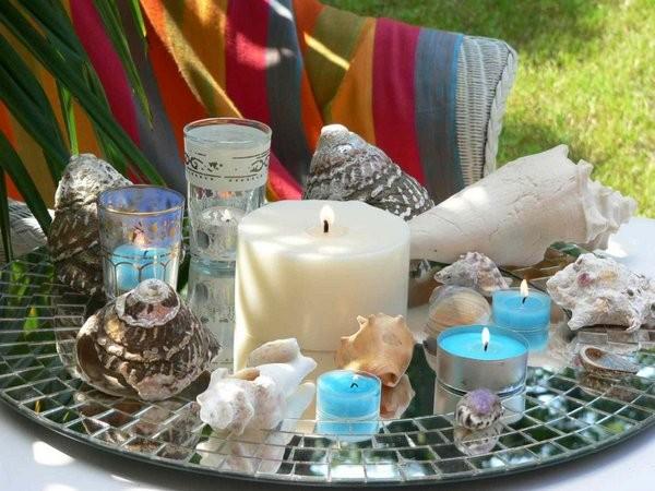 """Meerblau.... ... leuchten die farbigen Teelichte mit dem RAL-Gütezeichen und bilden - zusammen mit verschieden großen Muscheln - einen dekorativen """"Rahmen"""" für die große Solitär-Kerze in der Mitte. Tipp:. Die Teelichte mit dem RAL-Gütezeichen sind in vielen verschiedenen Farben erhältlich und geben jedem Arrangement - je nach Farbwahl - eine völlig neue Stimmung. Foto: Gütegemeinschaft Kerzen."""