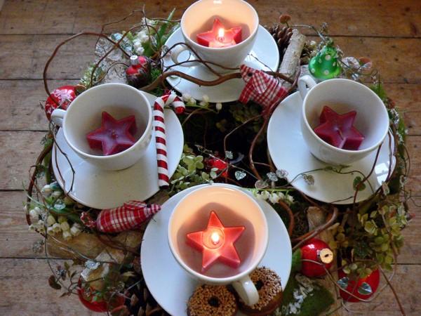 """""""Advents-Kaffeekranz"""". Ein echter Hingucker ist dieser besondere Adventskranz: In kleinen Tassen leuchten rote Sternlichte in RAL-Qualität (von WENZEL) und sorgen beim adventlichen Kaffeekranz für eine muntere Stimmung. Foto: Gütegemeinschaft Kerzen. Accessoires & Dekoration:  www.blumen-fuss.de (Düsseldorf)"""